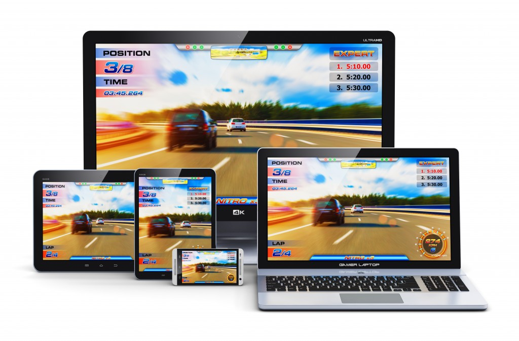 Creative abstract computer gaming and entertainment technology concept: modern black gamer desktop PC, laptop or notebook, tablet and metal glossy touchscreen smartphone with auto racing sport video game isolated on white background
