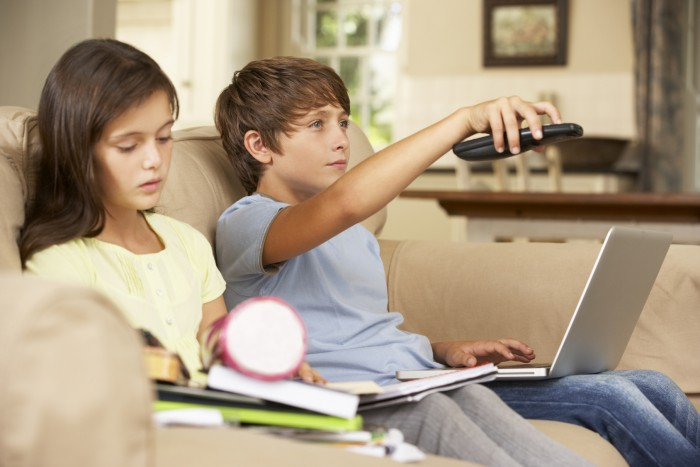 Two Children Distracted By Television Whilst trying To Do With Homework