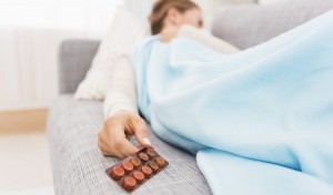 Closeup on pills pack in hand of ill young woman laying on sofa